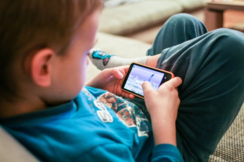 ребенок играет на мобильном телефоне